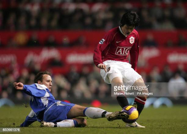 Manchester United's JiSung Park in tackled by Wigan's Andreas Johansson during the Barclays Premiership match at Old Trafford Manchester