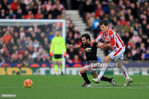 Manchester United's Juan Mata and Stoke City's Philipp Wollscheid battle for the ball
