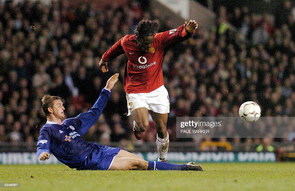 Manchester United's Louis Saha (R) is tacled by Leicester's Matthew Heath during their Premiership clash at Old Trafford in Manchester, Britain, 13 April 2004. AFP photo by Paul Barker