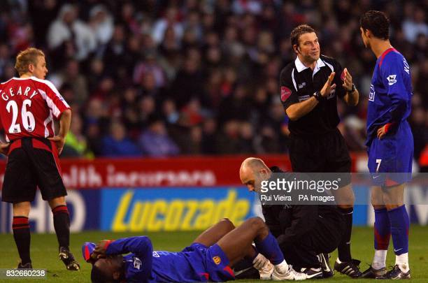 Manchester United's Louis Saha recieves Treatment while Cristiano Ronaldo Sheffield United's Derek Geary and Referee Mark Clattenburg look on