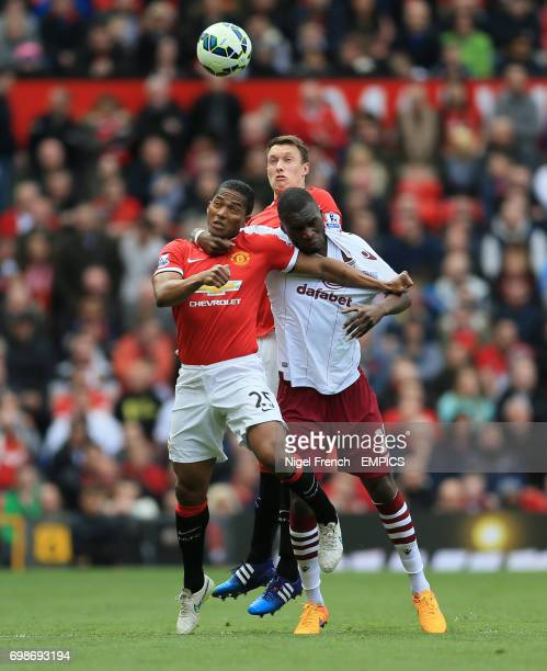 Manchester United's Luis Antonio Valencia and Phil Jones challenge Aston Villa's Christian Benteke for the ball