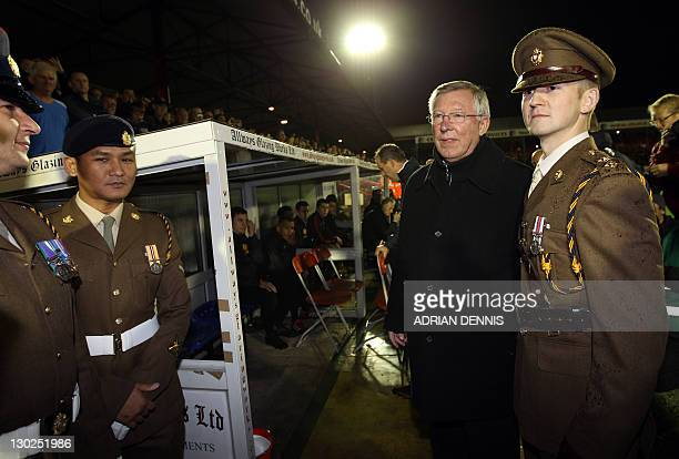 Manchester United's Manager Alex Ferguson poses with soldiers beside the dugout ahead of the Carling Cup fourth round football match between...