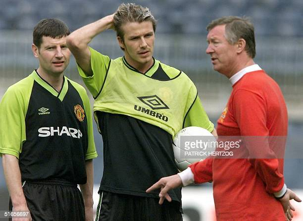 Manchester United's manager Alex Ferguson talks to midfielder David Beckham and defender Denis Irwin during the team's practice 25 May 1999 at the...