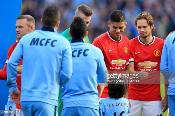 Manchester United's Marcos Rojo and Daley Blind shake hands with with mascot Benjamin the son of Manchester City's Sergio Aguero