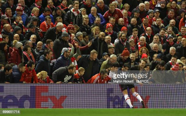 Manchester United's Marcos Rojo dives over the advertising hoardings to retreive the ball to the amusement of the Liverpool support