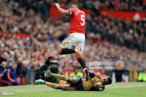 Manchester United's Marcos Rojo jumps over a challenge from Arsenal's Danny Welbeck