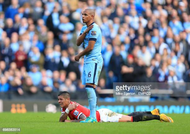 Manchester United's Marcos Rojo lies in pain after picking up a shoulder injury as Manchester City's Fernando checks on his condition