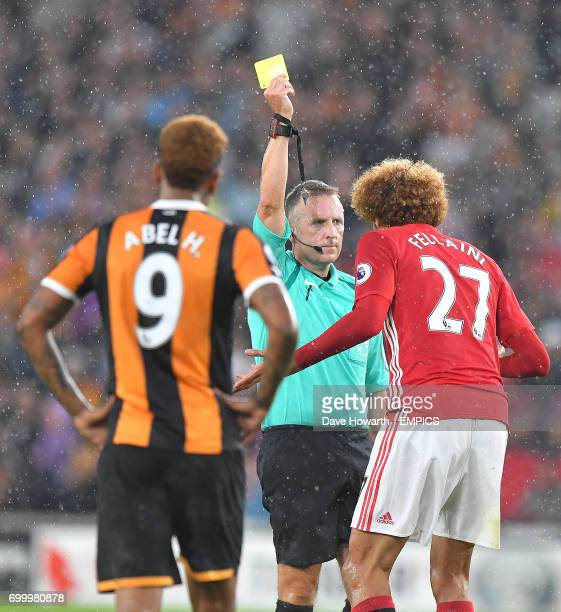 Manchester United's Marouane Fellaini is shown the yellow card by referee Jon Moss