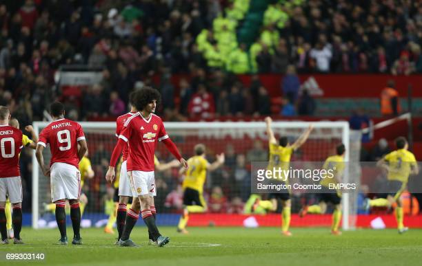 Manchester United's Marouane Fellaini looks dejected as Middlesbrough players run to celebrate winning on penalties