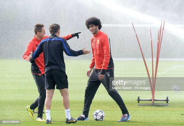 Manchester United's Marouane Fellaini shares a joke with Adnan Januzaj and Phil Neville during a training session at the AON Training Complex...