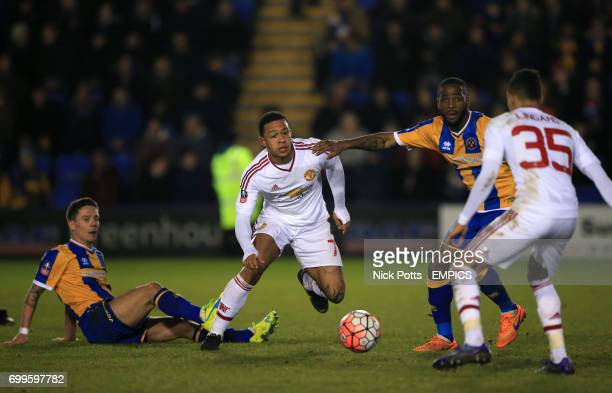 Manchester United's Memphis Depay and Shrewsbury Town's Abu Ogogo battle for the ball
