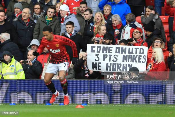 Manchester United's Memphis Depay warms up in front of fans holding up a banner