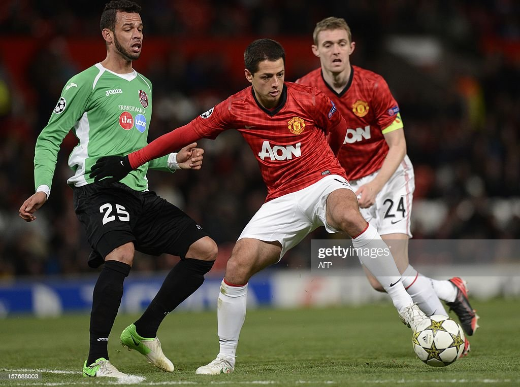 Manchester United's Mexican forward Javier Hernández (C) vies with Cluj's Brazilian midfielder Luis Alberto (L) during the UEFA Champions League group H football match between Manchester United and CFR Cluj-Napoca at Old Trafford in Manchester, north-west England, on December 5, 2012. Cluj won 1-0.
