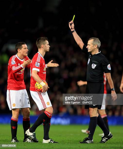 Manchester United's Morgan Schneiderlin is booked by referee Martin Atkinson