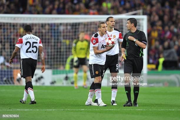 Manchester United's Nemanja Vidic and Rio Ferdinand argue with referee Viktor Kassai