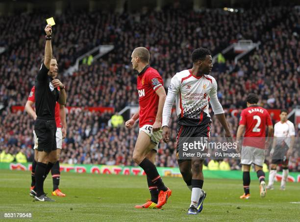 Manchester United's Nemanja Vidic is booked and sentoff by match referee Mark Clattenburg after fouling Liverpool's Daniel Sturridge in the penalty...