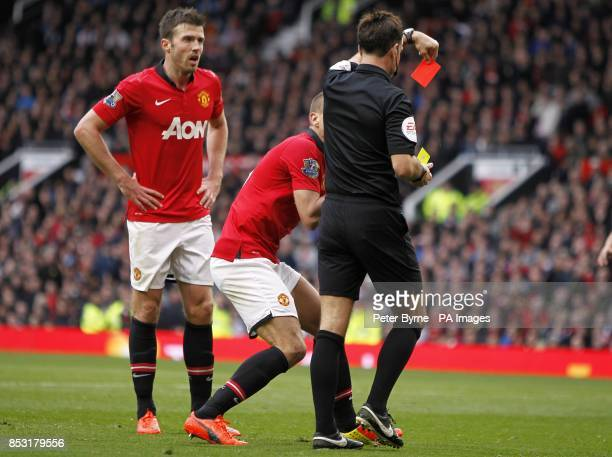 Manchester United's Nemanja Vidic is sent off by match referee Mark Clattenburg after fouling Liverpool's Daniel Sturridge in the penalty area