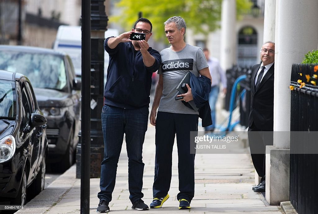 Manchester United's new Portuguese manager Jose Mourinho (R) poses for a 'selfie' photograph as he returns to his home in central London on May 27, 2016. Manchester United on Friday anointed Jose Mourinho as their new manager to launch a third bid in less than three years to transform the Red Devils into a title-winning force again. After three days of talks, Mourinho agreed a three-year contract on a bumper salary reportedly worth more than $20 million (19.5 million euros) a year. / AFP / JUSTIN
