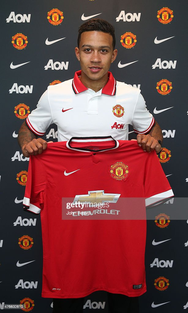 Manchester United's new signing Memphis Depay poses with his new shirt following the completion of his transfer at the Aon Training Complex on June...