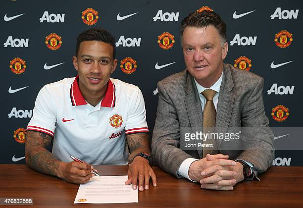 Manchester United's new signing Memphis Depay signs his contract in the presence of his new manager Louis Van Gaal at the Aon Training Complex on...