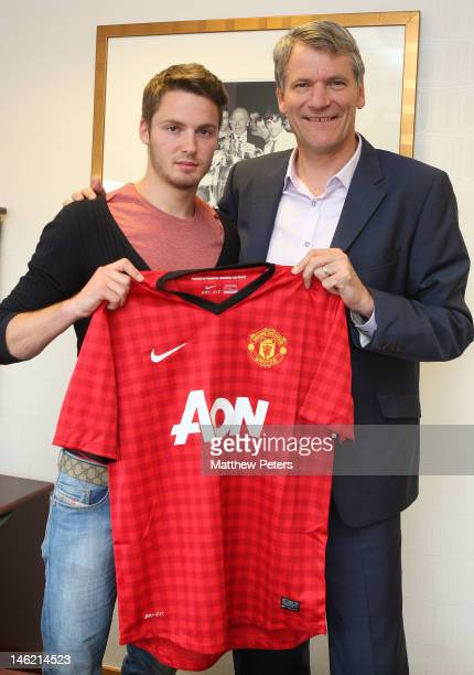 Manchester United's new signing Nick Powell from Crewe Alexandra poses with Manchester United's Chief Executive David Gill at Old Trafford on June 12...