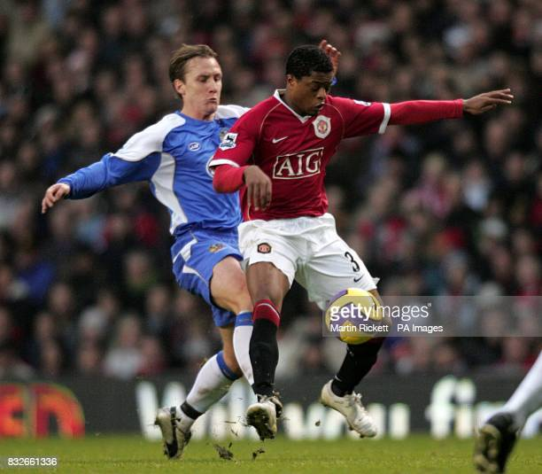Manchester United's Patrice Evra and Wigan Athletic's Andreas Johansson battle for the ball