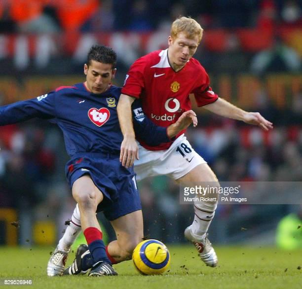 Manchester United's Paul Scholes battles with Portsmouth's Giannis Skopelitis