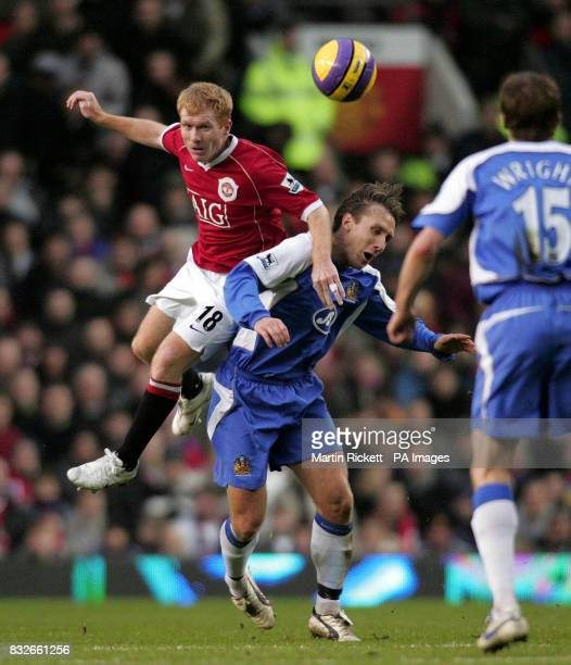 Manchester United's Paul Scholes tussles with Wigan's Andreas Johansson during the Barclays Premiership match at Old Trafford Manchester