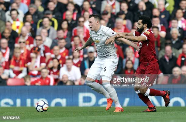 Manchester United's Phil Jones holds off the challenge from Liverpool's Mohamed Salah during the Premier League match between Liverpool and...