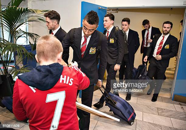 Manchester United's player Jesse Lingard signs an autograph to the club's fan Oscar Jones from Copenhagen as players arrive at Karup airport in...