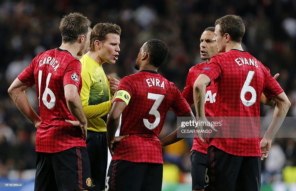 Manchester United's players argue with referee Felix Brych (2nd L) at the end of the UEFA Champions League round of 16 first leg football match Real Madrid CF vs Manchester United FC at the Santiago Bernabeu stadium in Madrid on February 13, 2013. The match ended in a 1-1 draw.