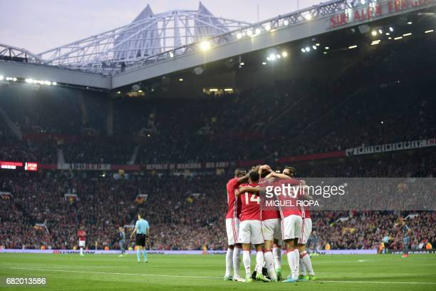 Manchester United's players celebrate with Belgian midfielder Marouane Fellaini after he scores the opening goal of the UEFA Europa League semifinal...