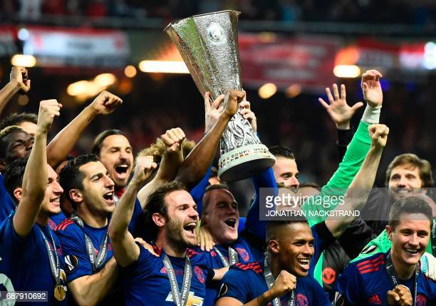 TOPSHOT Manchester United's players celebrate with the trophy after winning the UEFA Europa League final football match Ajax Amsterdam v Manchester...