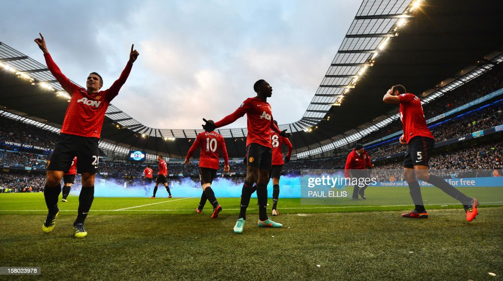 "Manchester United's players including Danny Wellbeck (C) celebrate Dutch striker Robin Van Persie's (L) late winning goal as English defender Rio Ferdinand (R) holds his head after being struck by an object thrown from the crowd with coins littering the pitch and a steward removing a smoke bomb during the English Premier League football match between Manchester City and Manchester United at The Etihad stadium in Manchester, north-west England on December 9, 2012. RESTRICTED TO EDITORIAL USE. No use with unauthorized audio, video, data, fixture lists, club/league logos or ""live"" services. Online in-match use limited to 45 images, no video emulation. No use in betting, games or single club/league/player publications."