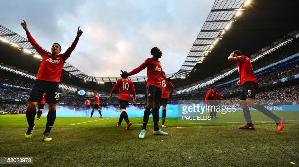 Manchester United's players including Danny Wellbeck celebrate Dutch striker Robin Van Persie's late winning goal as English defender Rio Ferdinand...