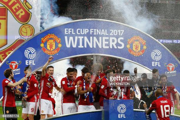Manchester United's players spray champagne as they celebrate with the trophy on the pitch after their victory in the English League Cup final...