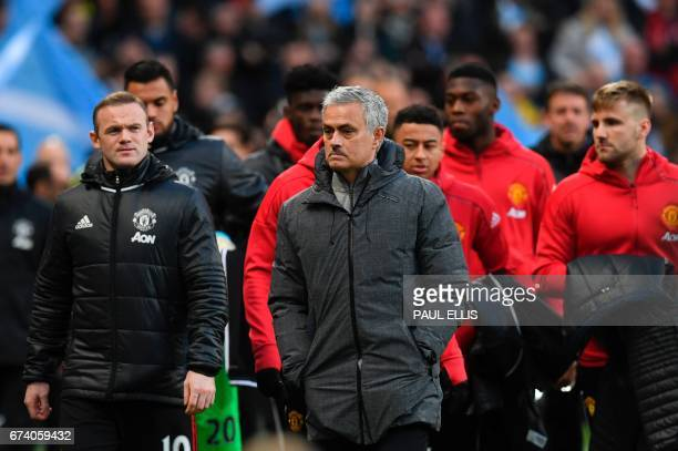 Manchester United's Portuguese manager Jose Mourinho arrives with the sustitutes including Manchester United's English striker Wayne Rooney during...