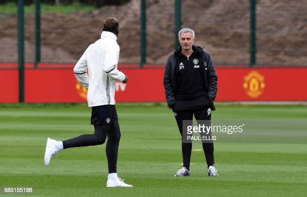 Manchester United's Portuguese manager Jose Mourinho chats to Manchester United's French midfielder Paul Pogba during a team training session as part...