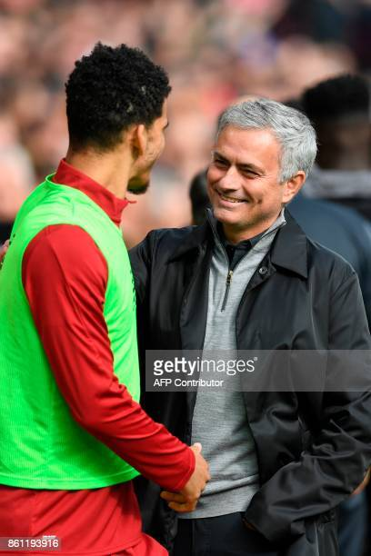 Manchester United's Portuguese manager Jose Mourinho chats with Liverpool's English striker Dominic Solanke ahead of the English Premier League...