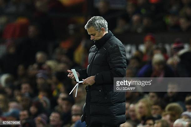 Manchester United's Portuguese manager Jose Mourinho checks his notes on the touchline during the UEFA Europa League group A football match between...
