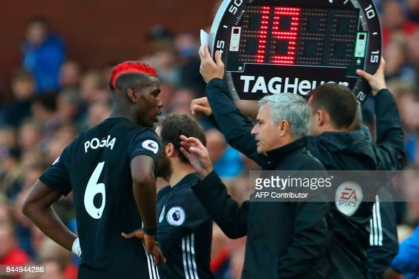 Manchester United's Portuguese manager Jose Mourinho gives instructions to Manchester United's French midfielder Paul Pogba during the English...