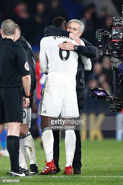 Manchester United's Portuguese manager Jose Mourinho hugs Manchester United's French midfielder Paul Pogba following the English Premier League...