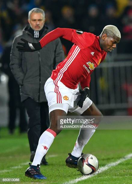 Manchester United's Portuguese manager Jose Mourinho looks at Manchester United's French midfielder Paul Pogba as he controls the ball during the...