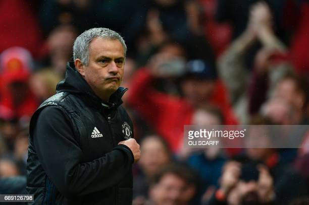 Manchester United's Portuguese manager Jose Mourinho points at the badge on his chest as he leaves the pitch at the end of the English Premier League...