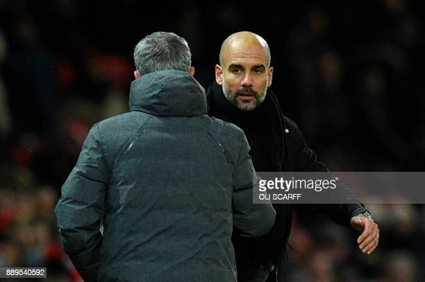 Manchester United's Portuguese manager Jose Mourinho shakes hands with Manchester City's Spanish manager Pep Guardiola at the end of the English...