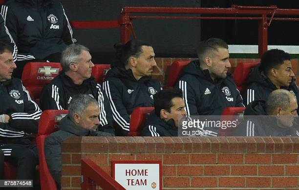 Manchester United's Portuguese manager Jose Mourinho sits in the Home Team dugout with members of his staff and substitutes Manchester United's...