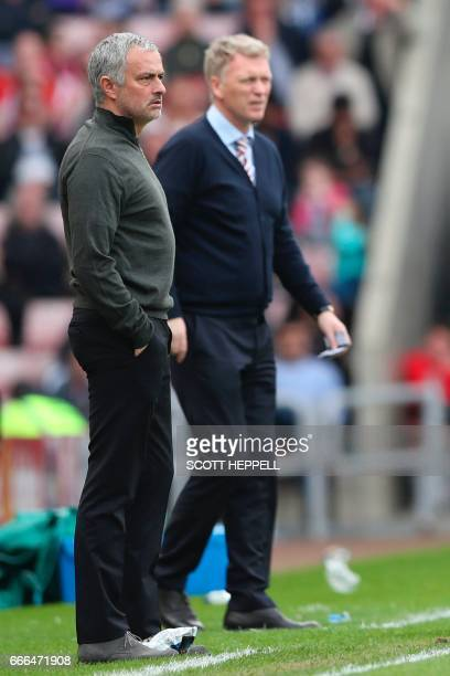 Manchester United's Portuguese manager Jose Mourinho stands with Sunderland's Scottish manager David Moyes on the touchline during the English...