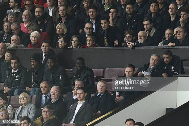 Manchester United's Portuguese manager Jose Mourinho talks with a member of his staff as he sits in the Directors Box after being sent off with...