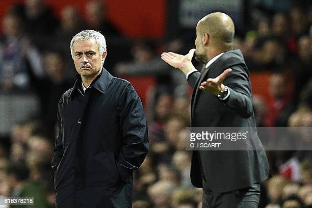 Manchester United's Portuguese manager Jose Mourinho watches as Manchester City's Spanish manager Pep Guardiola gestures on the touchline during the...