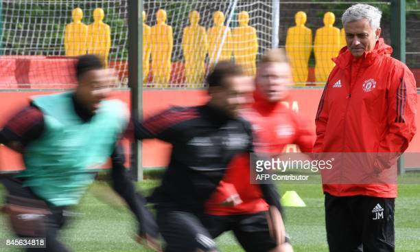 Manchester United's Portuguese manager Jose Mourinho watches his players during a team training session at the club's training complex near...